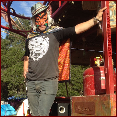 Mark Goerner, a business man (as his hat clearly indicates), models a reversible cape while standing on the Pyrobar at the Lucidity Festival in the Santa Barbara Mountains.